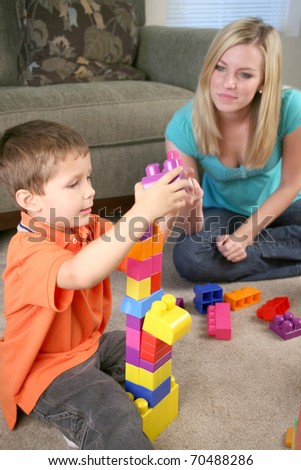 A mother and young son playing with blocks - stock photo
