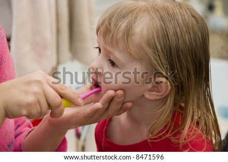 A mother brushes her daughter's teeth - stock photo