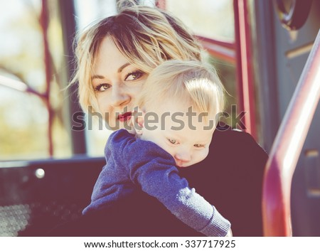 A Mother Comforts her Crying Toddler on a Playground - stock photo