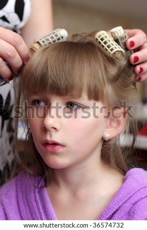 A mother curls daughter's hairs by heat retro rollers