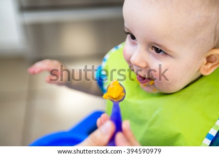 A Mother feeding hungry baby in the highchair indoors - stock photo