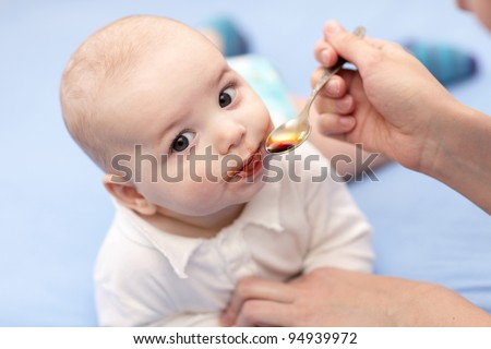A mother giving a spoon of iron syrup to her baby - stock photo