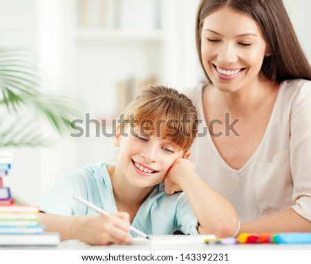 A mother helping her daughter with homework. - stock photo