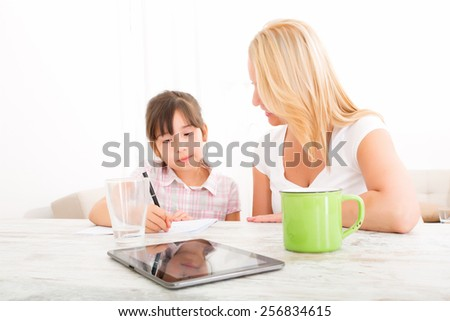 A mother helping her daughter with the homework. - stock photo