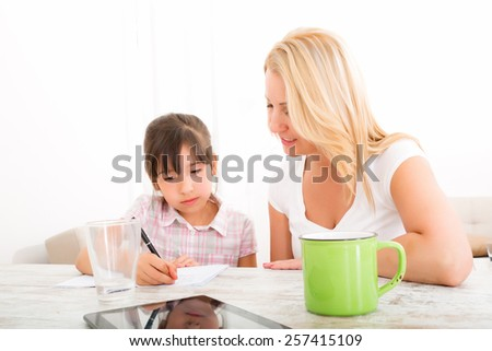 A mother helping her daughter with the homework.