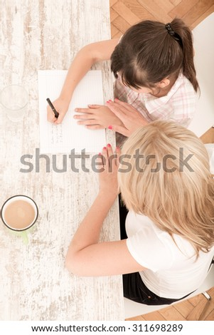 A mother helping her daughter with the homework seen from above. - stock photo