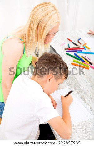 A mother helping his son with his homework.  - stock photo
