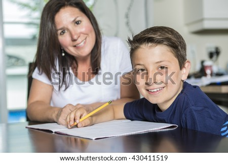 A Mother Helping Son With Homework At Table - stock photo