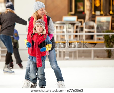 a mother helps her son learn to ice-skate - stock photo