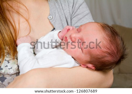 A mother holds her newborn baby in her arms while looking down at him with a happy look. The baby boy is in comfort and trusts his mom fully. He is sleeping peaceful.y.