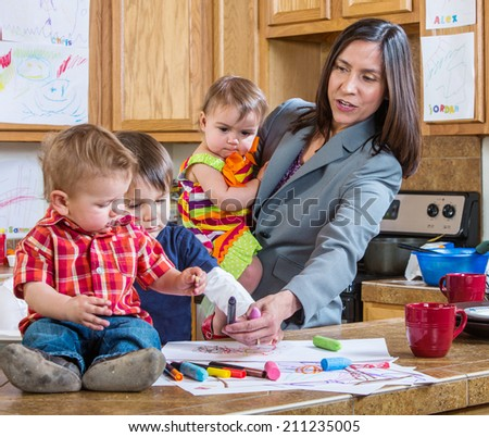 A mother in the kitchen plays with her children - stock photo