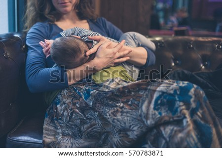A mother is breastfeeding her baby in a restaurant