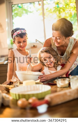 A mother is cooking with her two daughter of four and seven years old. They are smiling, wearing casual clothes. The woman is helping her youngest mixing the ingredients in a large bowl. - stock photo