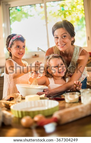 A mother is cooking with her two daughters of four and seven years old. They are smiling, wearing casual clothes. The sisters are mixing the ingredients in a large bowl with a whisk.Shot with flare - stock photo