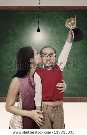A mother is kissing her son for winning a trophy at school