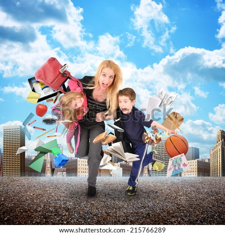 A mother is late for school and work while rushing with her children for a funny stress concept with a city in the background. There are objects flying away from them.  - stock photo