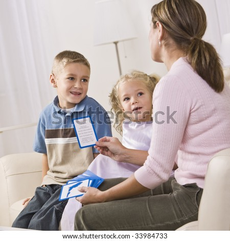 A mother is playing cards with her children.  They are smiling and looking at her.  Vertically framed shot. - stock photo