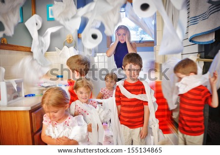A mother is shocked and full of stress while the children make a mess in the bathroom with toilet paper. - stock photo