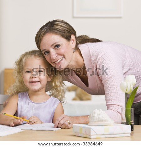 A mother is sitting with her young daughter and watching her draw.  They are smiling at the camera.  Square framed shot.