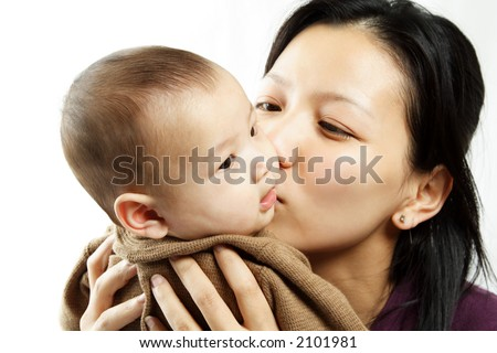 A mother kissing her cute baby son - stock photo