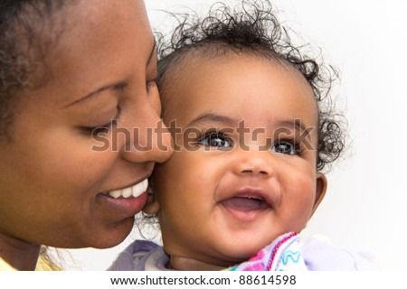 A mother kissing her smiling baby girl on the cheeks - stock photo