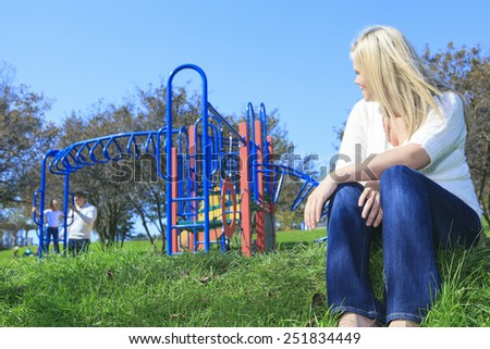 A mother look at boyfriend and children play on the playground - stock photo