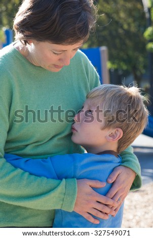 A mother parents her son at a playground - stock photo