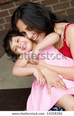 A mother plays with her daughter at the doorstep of the house - stock photo