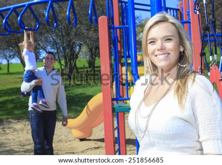 A mother portrait and boyfriend and children play on the playgroundg - stock photo