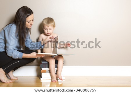 A Mother reading with her son siting on books - stock photo
