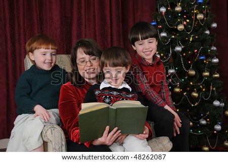A mother reads Christmas stories to her three little boys - stock photo
