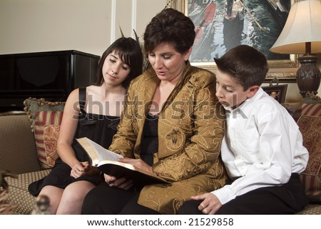 A mother reads from the Bible to her two children. - stock photo