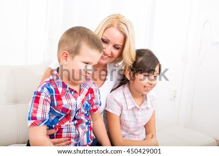 A mother relaxing on a sofa with her daughter and her son.
