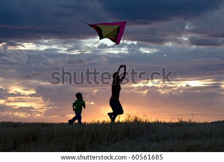 A mother runs with a kite while the son follows behind during sunset. - stock photo