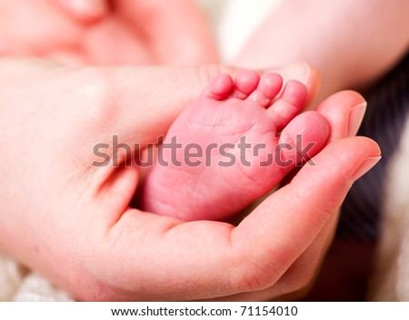 A mother's hand holding the foot of her baby