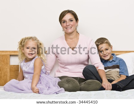 A mother sits on a bed with her son and daughter as they smile at the camera. Horizontally framed shot. - stock photo