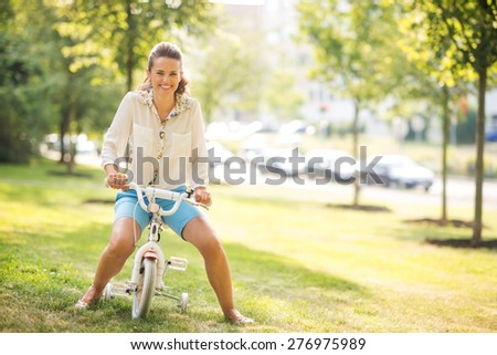 A mother sits playfully, smiling, on her daughter's training bicycle, pretending to ride. The setting is an urban park, full of trees and green grass. - stock photo