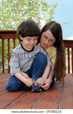 A mother teaches her preschool boy how to tie his shoes - stock photo