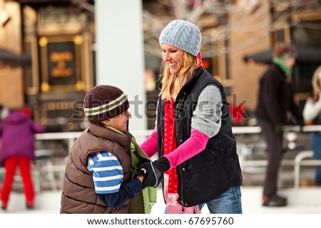 A mother teaches her son to ice skate.  Room for copy. - stock photo