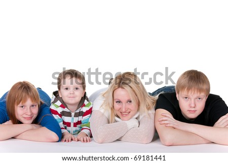 A mother, two sons and daughter are smiling, lying on the studio floor; isolated on the white background - stock photo