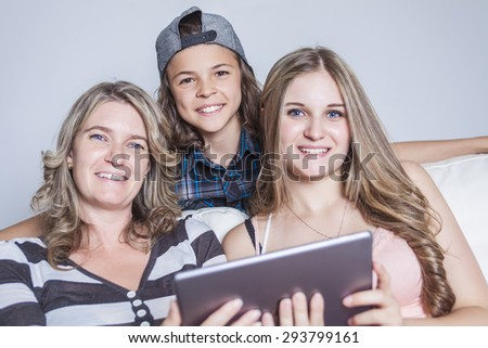 A Mother using digital tablet while sitting on sofa at home - stock photo