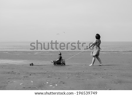 a mother walking with her son on the beach in black and white. She is pulling a car where the boy is in. The boy is pulling on his own little car. Two seagulls are flying in the sky. - stock photo