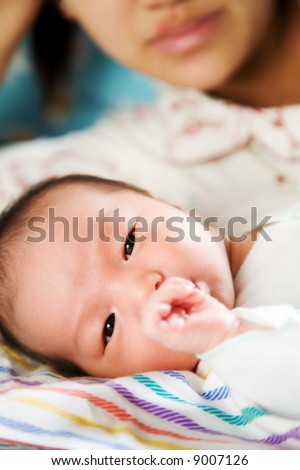 A mother watching her newborn baby sucking his thumb - stock photo