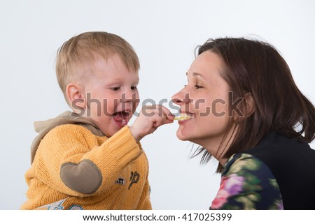 A mother watching her son eating fruit arranged into a frog to make the meal interesting to the child. - stock photo