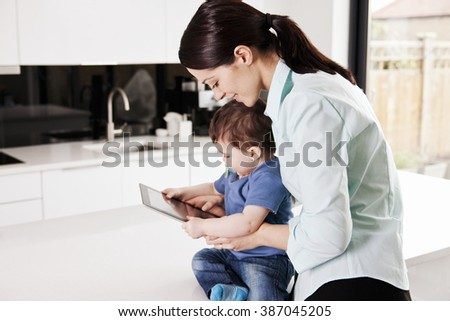 A mother with her baby son, looking at a digital tablet - stock photo