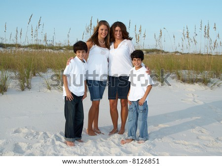 A mother with her children on the beach. - stock photo