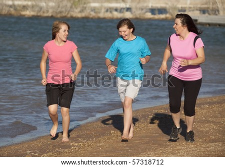 A mother with her daughters running on the beach while they laugh and smile at each other. - stock photo