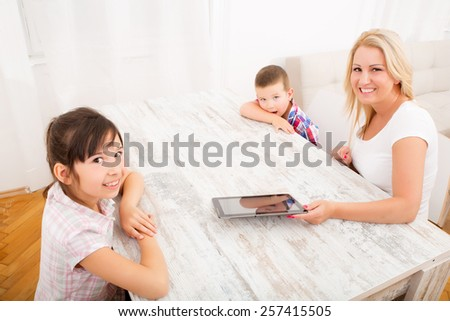 A mother with her kids using a tablet PC at home.  - stock photo