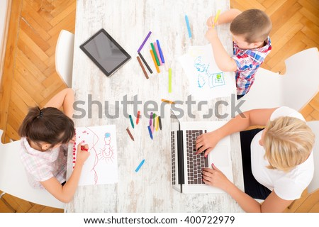A mother with her kids with at a laptop at home. - stock photo