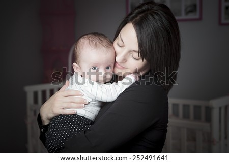 A mother with is baby on the baby room. - stock photo